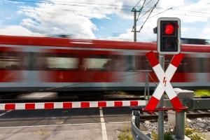 Eine rote Ampel am Bahnübergang weist darauf hin, dass alle stehen bleiben müssen.