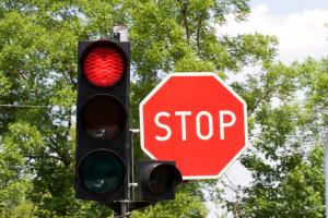 Die Ampel und das Stoppschild sind Verkehrszeichen, die die Vorfahrt regeln.