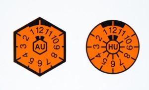 Früher gab es auf einem Nummerschild für die HU und AU jeweils eine Prüfplakette. Heute existiert nur noch die runde HU Prüfplakette.